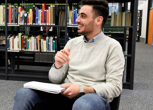 Scholarship recipient sitting in library smiling to something off camera